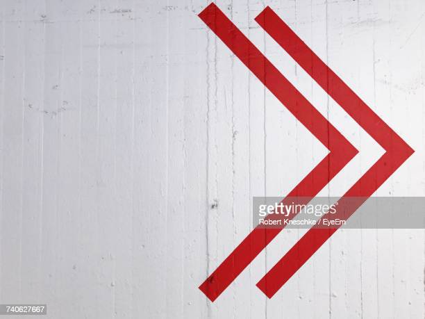 red arrow symbol on white wall - guidance stock pictures, royalty-free photos & images