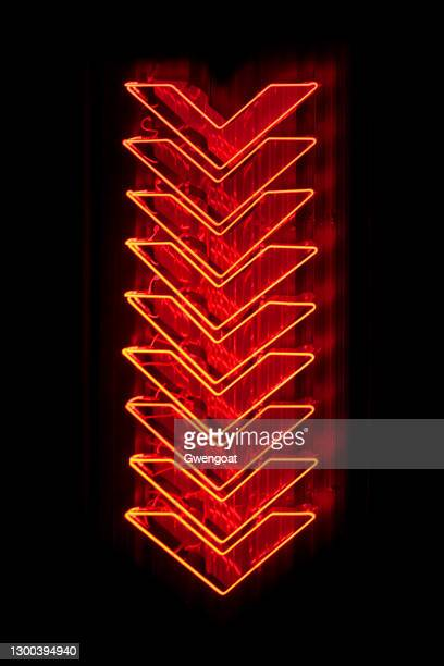red arrows neon light pointing down - gwengoat stock pictures, royalty-free photos & images