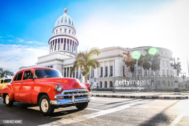red authentic vintage car moving in front of el capitolio - cuba foto e immagini stock