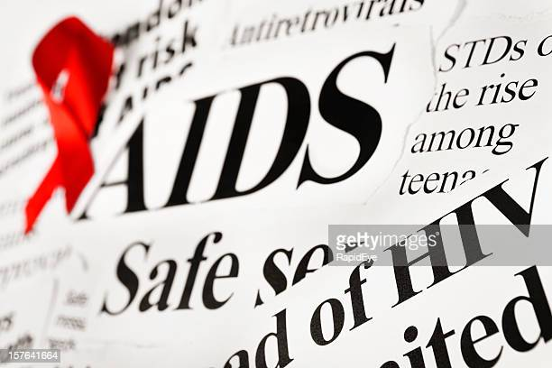 red awareness ribbon on aids related newspaper headlines - aids stock pictures, royalty-free photos & images