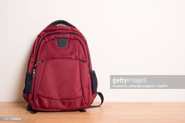 red backpack on hardwood floor against wall - rucksack stock pictures, royalty-free photos & images