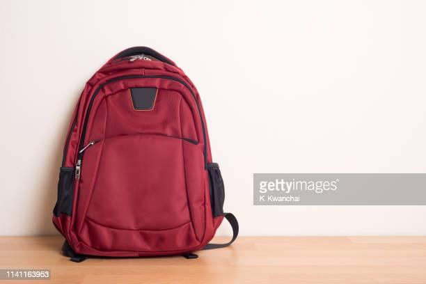 red backpack on hardwood floor against wall - rucksack stock-fotos und bilder