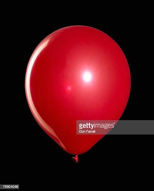 Red balloon against blackground