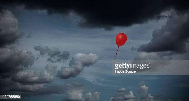 Red balloon floating through dark sky