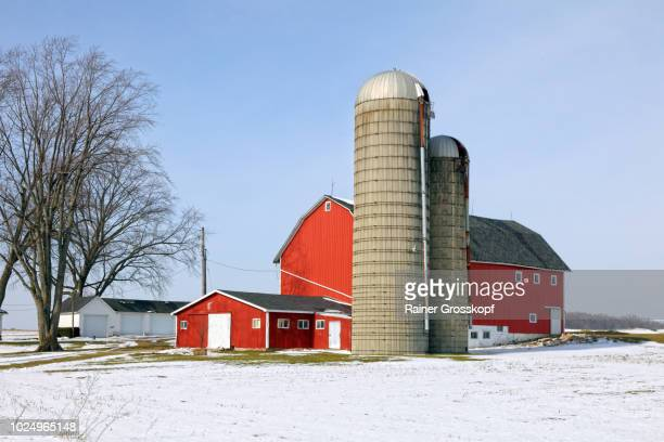 Red barn and farm in a snow-covered winter landscape