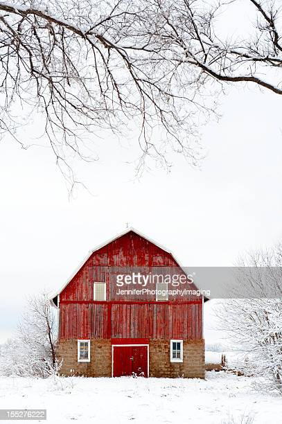 Red barn in snowy field during winter
