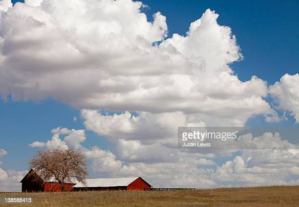 Red Barn on open plain with big white cloud
