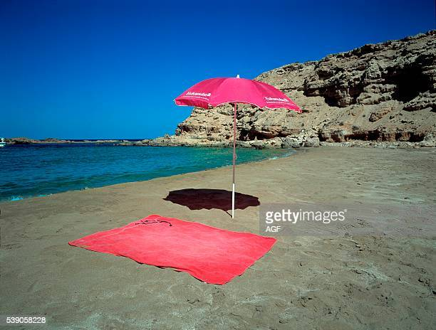 Red beach towel and red umbrella in the sand near the sea