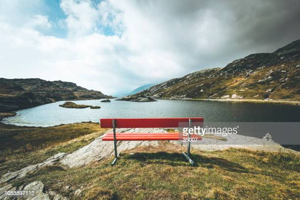red bench with a view, mountain lake san bernardino, switzerland - bench stock pictures, royalty-free photos & images