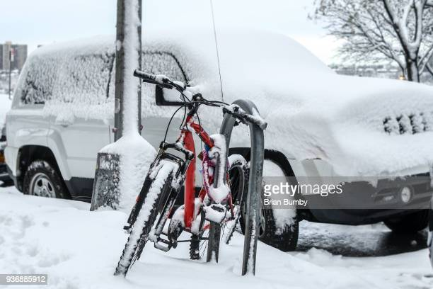 Red bicycle covered in snow on street