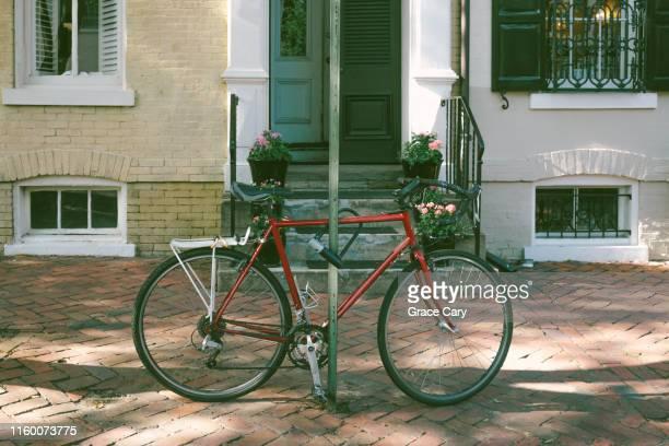 red bike parked on brick sidewalk - バージニア州 アレクサンドリア ストックフォトと画像