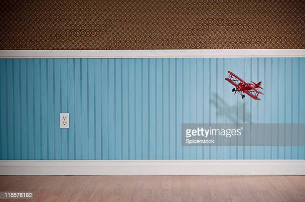 red biplane flying in empty room - wainscoting stock photos and pictures