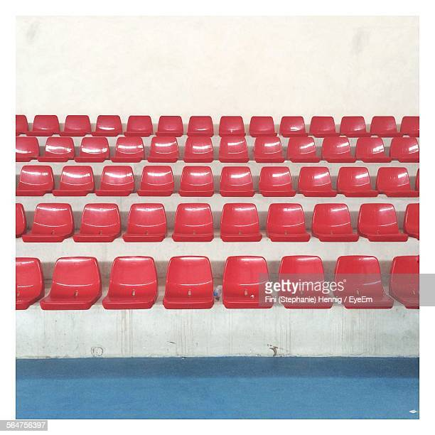 red bleachers at stadium - empty bleachers stockfoto's en -beelden