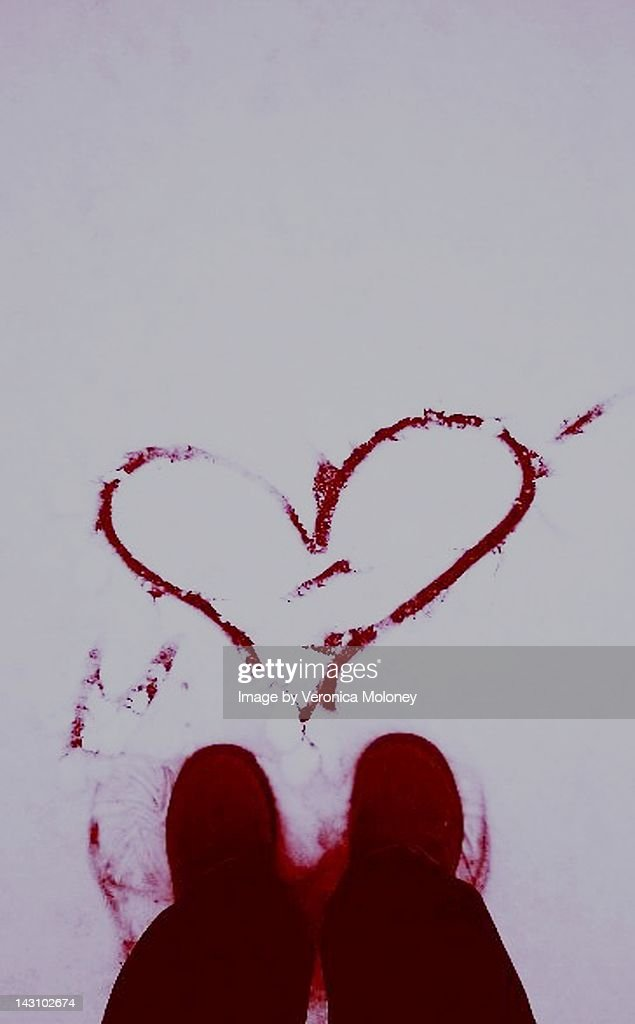 Red blood hear drawn on snowy valentines day : Stock Photo