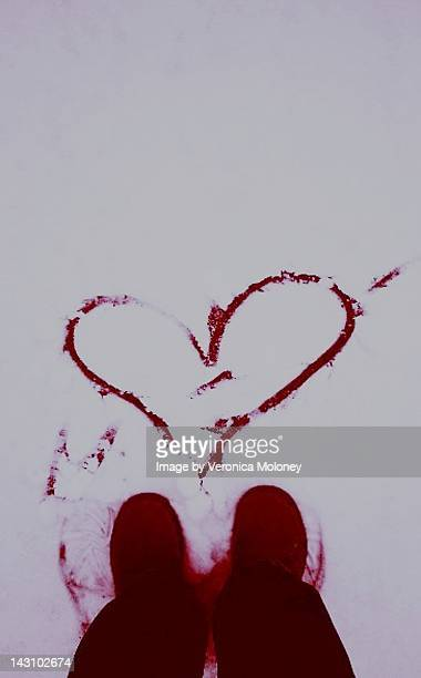 red blood hear drawn on snowy valentines day - bloody heart stockfoto's en -beelden
