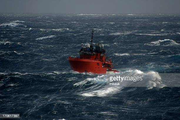 Red boat in the sea during a storm