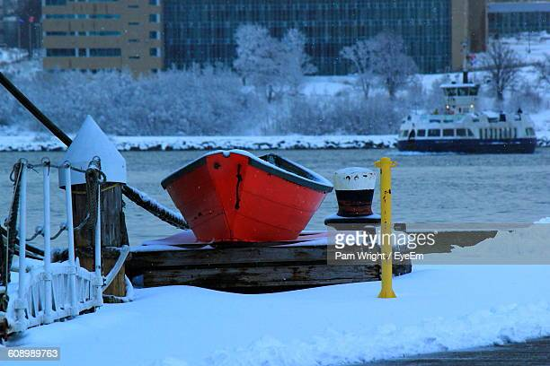 Red Boat Moored At Port Against Buildings In Winter