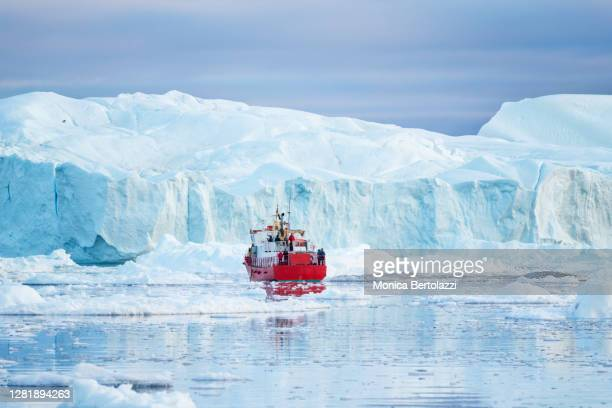 a red boat sailing among icebergs in ilulissat - eismeer stock-fotos und bilder