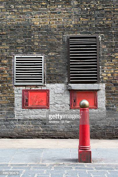 red bollard against bricked wall with vents. - bollard stock photos and pictures