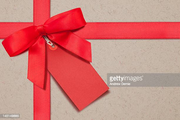 red bow and gift tag - andrew dernie stock pictures, royalty-free photos & images