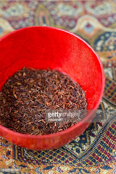 Red bowl of dried rooibos tea on cloth