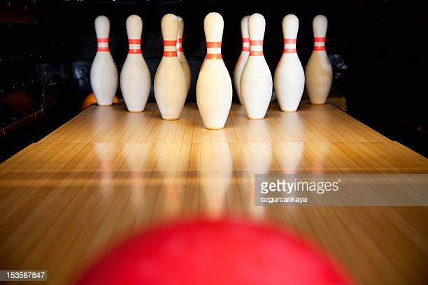 A red bowling ball rolling towards ten upright bowling pins