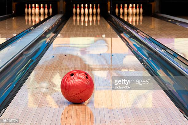 Red bowling ball sitting in middle of newly oiled lane