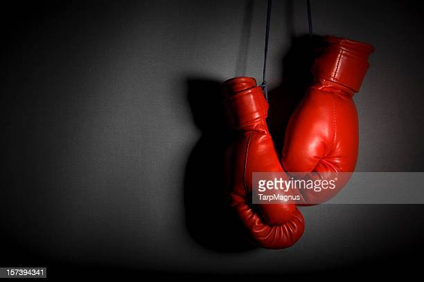 red boxing gloves hanging against grey wall - boxing gloves stock photos and pictures