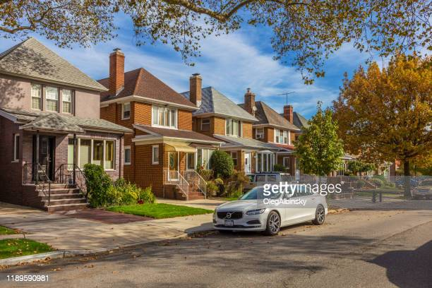red brick houses along brooklyn street with luxury volvo sedan parked along the street, and blue sky, new york, usa. - sedan stock pictures, royalty-free photos & images
