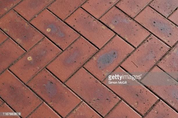 red brick paving in a herringbone pattern - herringbone floor stock photos and pictures