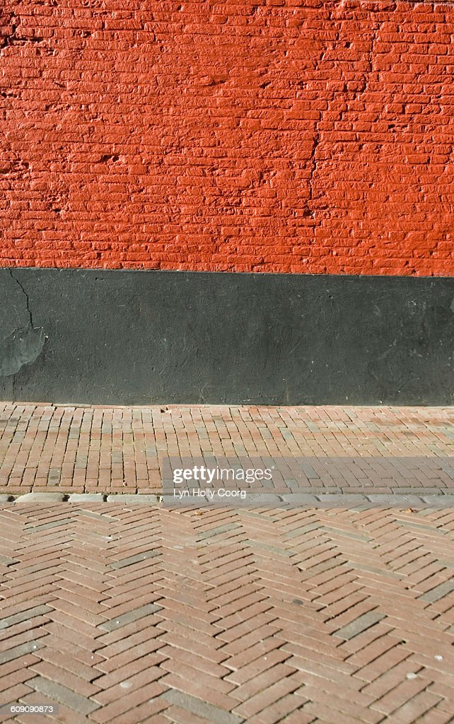 Red brick wall and paved street : Stock Photo