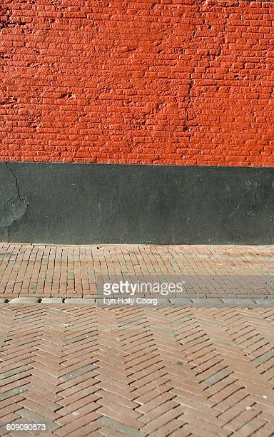 red brick wall and paved street - lyn holly coorg photos et images de collection