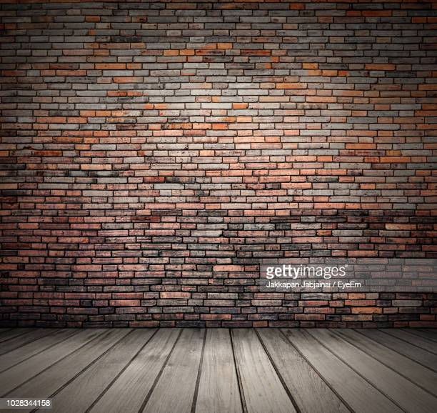 red brick wall by wooden floor - brick wall stock pictures, royalty-free photos & images