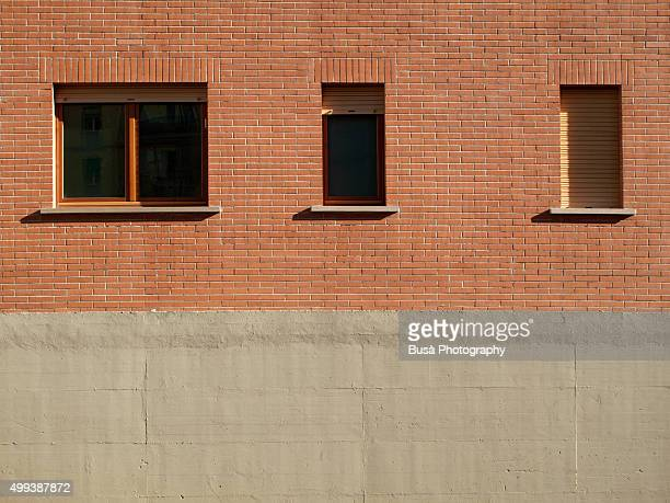 Red brick wall with concrete base and three windows