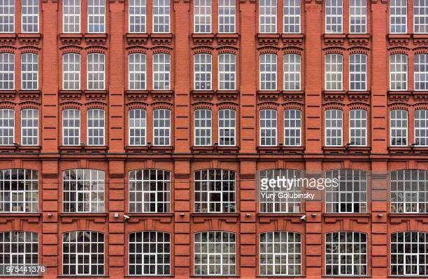 red brick wall with white frame windows - fachada arquitectónica fotografías e imágenes de stock