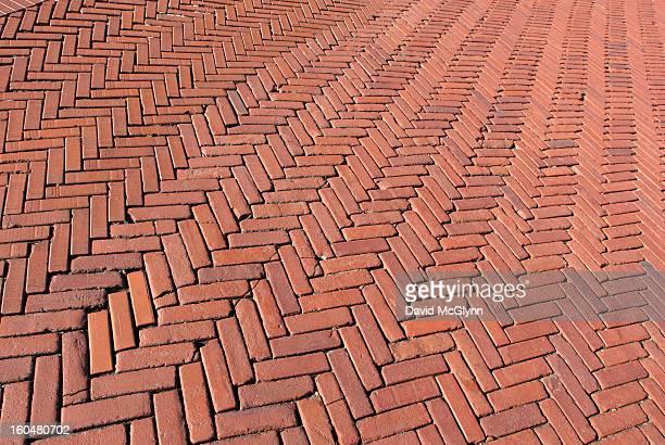 red bricks in a herringbone pattern - herringbone fotografías e imágenes de stock