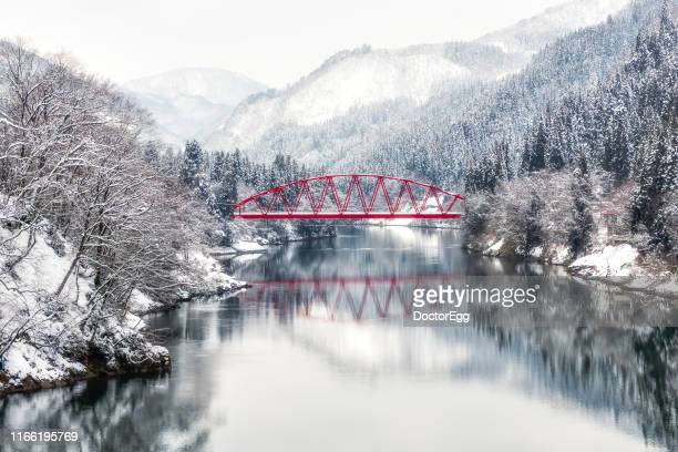red bridge across tadami river in winter near aizu miyashita station , mishima, fukushima, japan - 東北地方 ストックフォトと画像