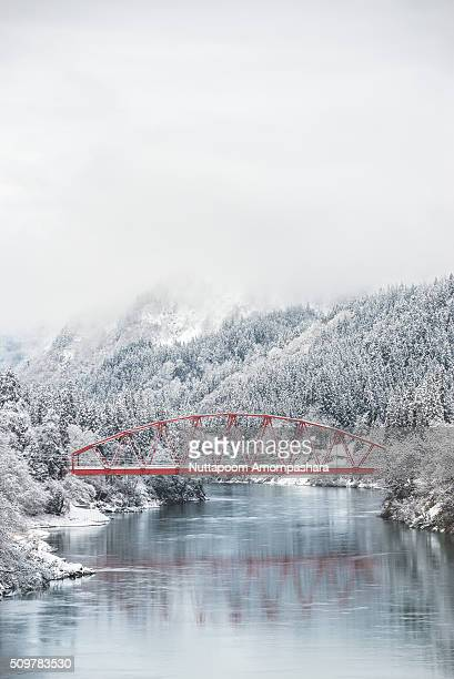 red bridge with snowy river bank - mishima city stock photos and pictures