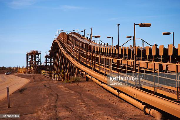 red brown conveyor belts on the iron ore mine site - iron ore stock photos and pictures