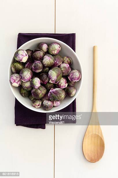 Red brussels sprouts in bowl, wooden spoon