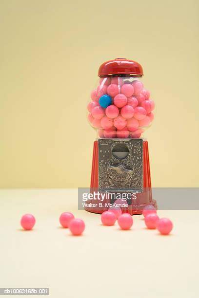 Red bubble gum ball machine with one blue and pink gum balls inside and some scattered outside