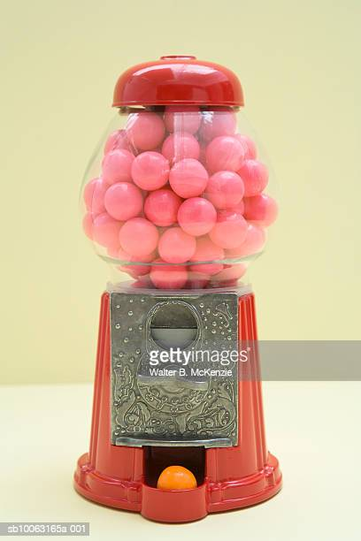 red bubble gum machine with pink gum balls inside and one orange ball dispensed - gumball machine stock pictures, royalty-free photos & images