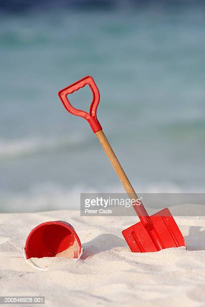 Red bucket and spade in sand on beach