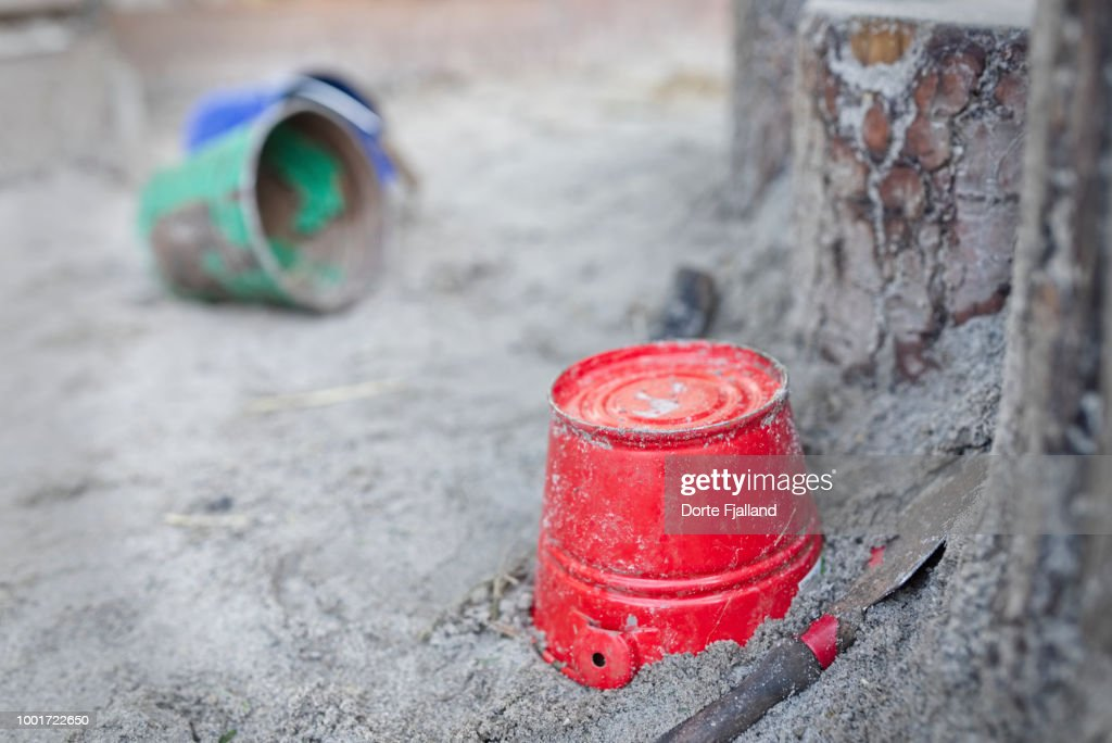 Red bucket in a sandbox with a green and a blue bucket in the background : Foto de stock
