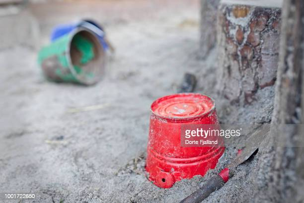 Red bucket in a sandbox with a green and a blue bucket in the background