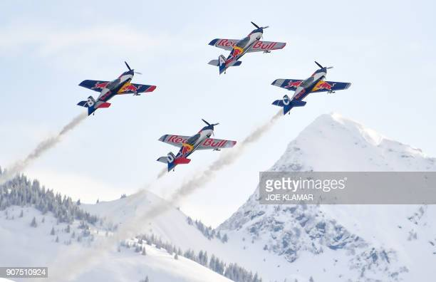 A Red Bull aerobatic team performs in the sky during an airshow during the FIS Alpine World Cup in Kitzbuehel Austria on January 20 2018 / AFP PHOTO...