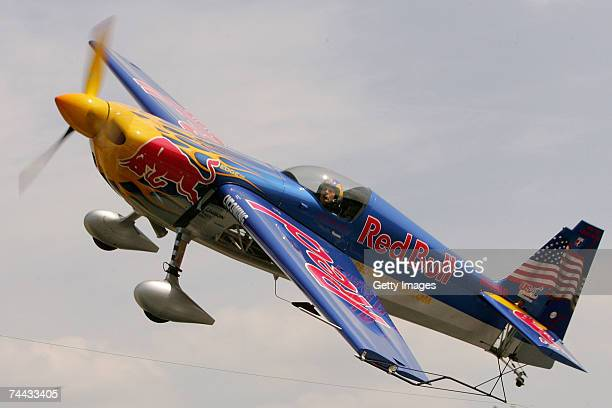 Red Bull Air Race world champion Kirby Chambliss flying his Zivko EDGE airplane does aerobatics tricks before raceing against a Chevy Cobalt dragster...
