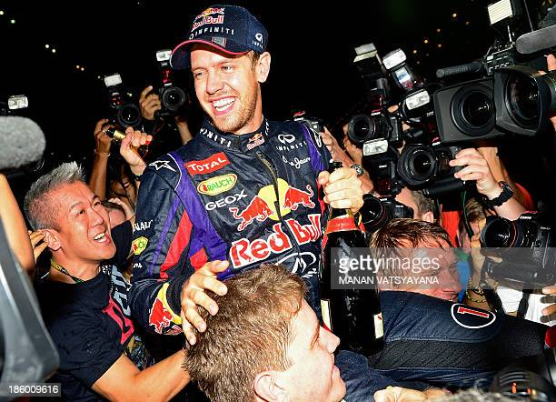 Red Bull driver Sebastian Vettel of Germany celebrates with his teammates after winning the Formula One Indian Grand Prix and his fourth successive...
