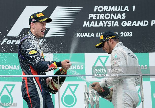 Red Bull driver Sebastian Vettel of Germany sprays champagne with thirdplaced Mercedes driver Lewis Hamilton of Britain on the podium after winning...