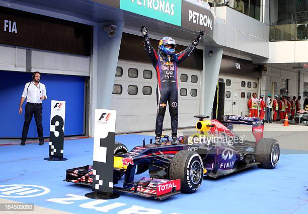 Red Bull driver Sebastian Vettel of Germany stands on his car as he celebrates his victory at the end of the Formula One Malaysian Grand Prix in...